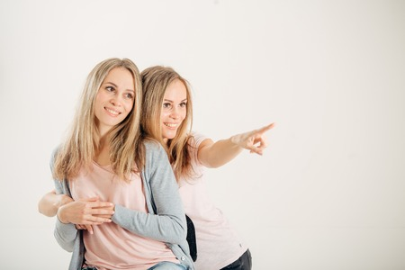 Two attrative sisters twins pointing over white background