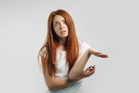 Puzzled and clueless young redhead woman with arms out