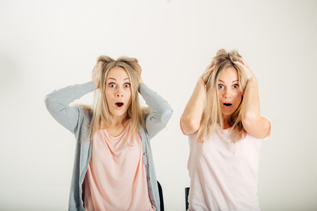 Surprised girl looking at her sister twin over white background Stock Photo