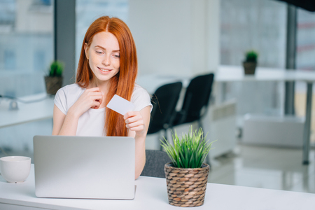 Woman buying online with laptot and looking at credit card