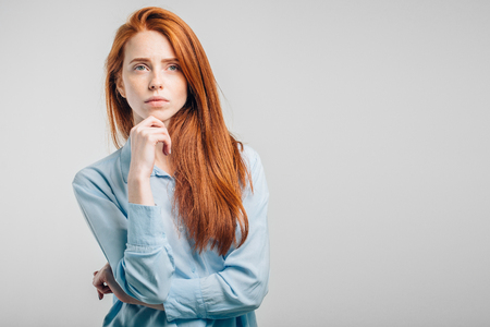 redhead young Caucasian woman holding arm on her chin and looking up sideways Stock Photo