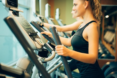 woman exercising on cross trainer machines.
