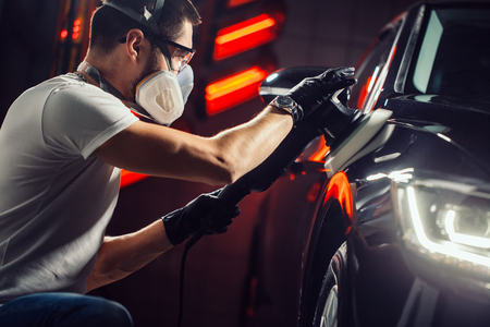Car detailing - man with orbital polisher in auto repair shop. Selective focus. Archivio Fotografico