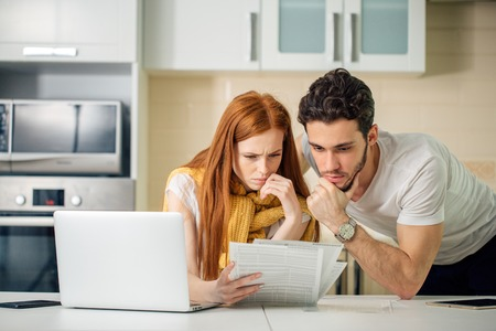 presupuesto de administración familiar, revisar sus cuentas bancarias usando una computadora portátil en la cocina