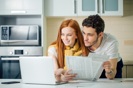 Happy couple at home paying bills with laptop Фото со стока - 92314911
