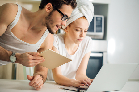 Couple with laptop and tablet in kitchen