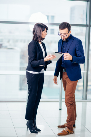 Businesswoman with male colleague using tablet computer
