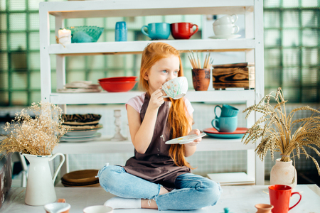 redhead girl sitting at clay workshop studio with many cup