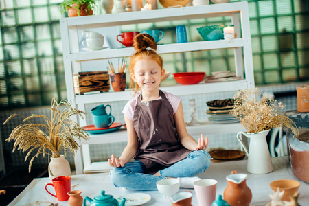 girl wih many cups made from clay sitting in pottery studio Stock Photo