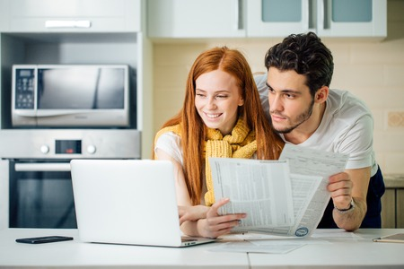 wesoła młoda para obliczania rachunków w domu