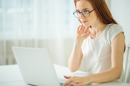 Concentrated redhead businesswoman working on laptop in bright modern office