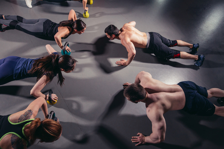 Group adults doing push up exercises indoor