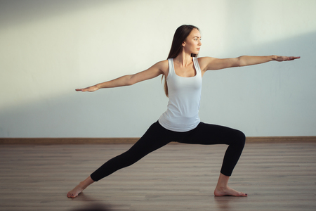 woman practicing yoga, standing in Warrior one exercise, Virabhadrasana