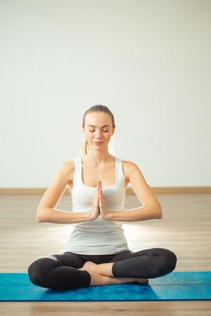 woman practicing yoga, sitting in Padmasana, exercise, Lotus pose, namaste
