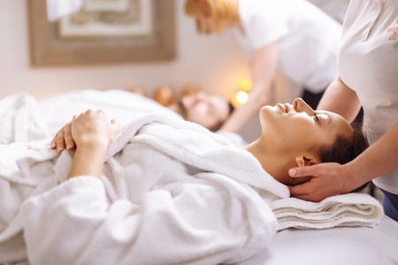 Young couple receiving head massage at beauty spa Stock Photo - 93681076