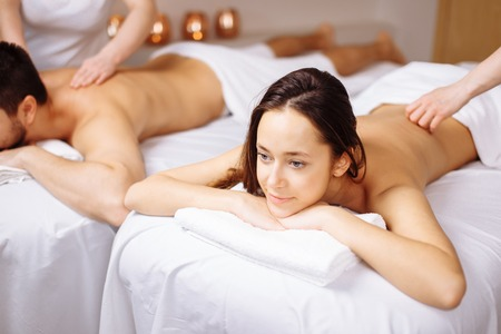 Happy couple getting massage at spa Stock Photo