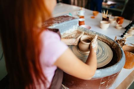 スタジオで車輪を投げる女性陶芸家。粘土ワークショップ