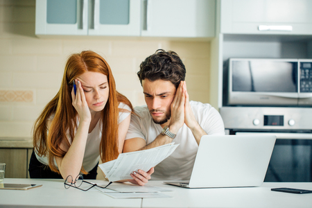 Worried couple paying their bills online with laptop at home in living room Stock Photo