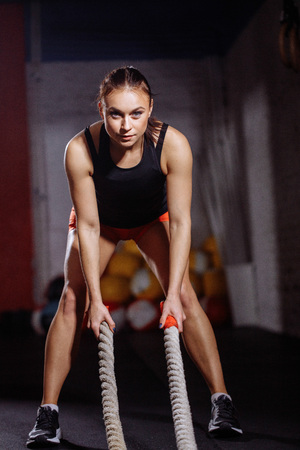 Fit sportswoman working out in gym doing cross fit exercise with ropes