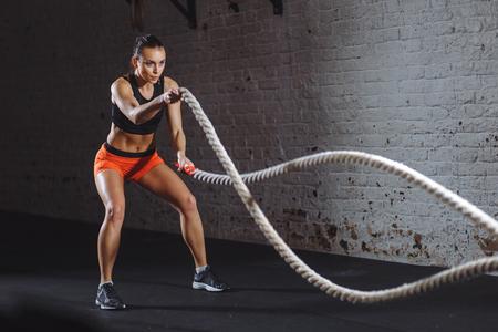 Die athletische Frau, die Kampfseil tut, trainiert an der Turnhalle Standard-Bild