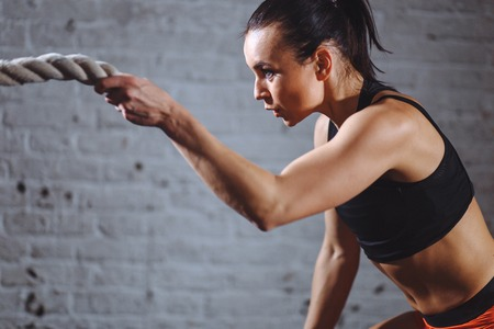 close up photo of Athletic woman doing battle rope exercises at gym Imagens