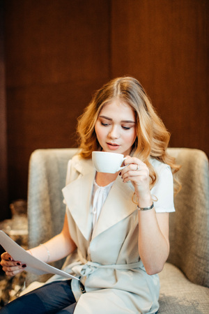 businesswoman reading document. Female examining papers with coffee