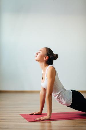 woman practicing yoga indoor. Beautiful girl practice cobra asana in class