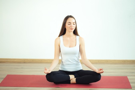 Young woman meditates while practicing yoga Stock fotó