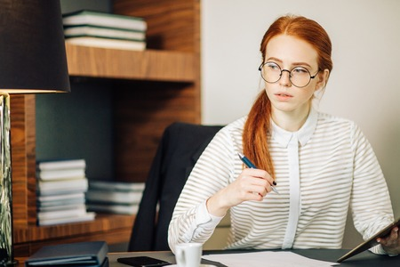 Woman writing on paper with digital tablet computer in office room