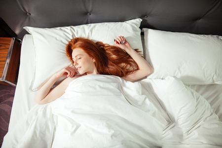 sleeping young woman lies in bed with eyes closed. top view 写真素材