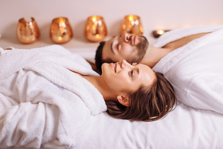 man and woman lying down on massage beds at luxury spa and wellness center