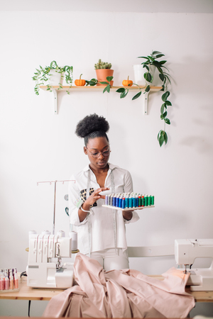 african seamstress holding coils with threads