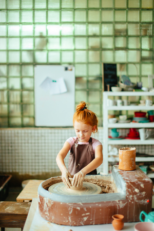 redhead Child sculpts from clay pot. workshop on modeling on potters wheel.