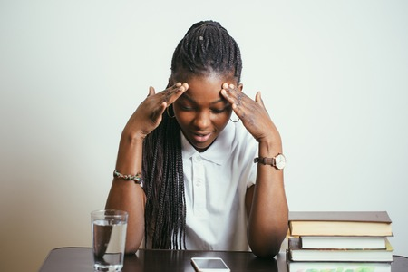 african young woman sitting at table with books at home Stock Photo