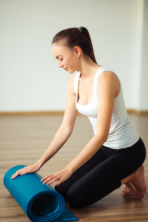 woman practicing yoga, preparing for exercise, unrolling or rolling yoga mat Stock Photo