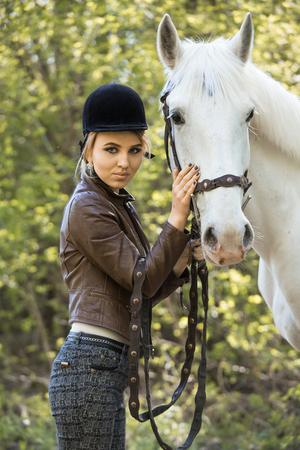 beautiful girl stroking horse outside Stock Photo