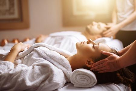 Jovem casal lindo feliz desfrutando de massagem na cabeça no spa Foto de archivo - 94491344