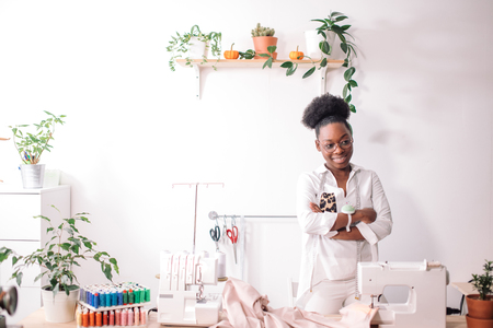 smiling seamstress looking at camera with sewing machine