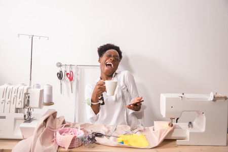 Laughing seamstress sewing in studio Stock Photo