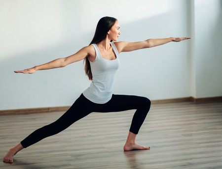 young woman wearing white tank top working out, doing yoga exercise