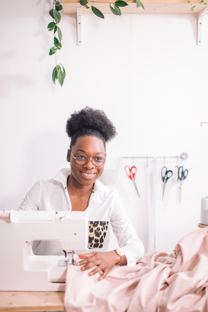 african seamstress sews clothes Stock Photo