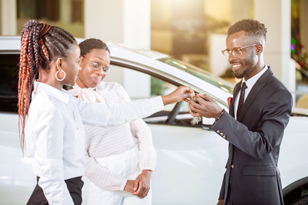 Sales situation in car dealership, young african couple gets the key for new car 写真素材