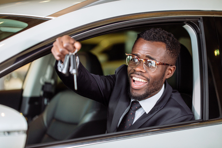 Young African Businessman Sitting In A Car Showing Car Key