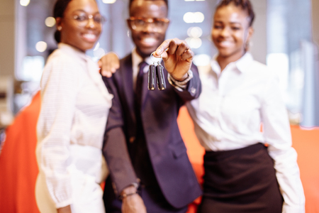 car salesman and two woman showing key of new car