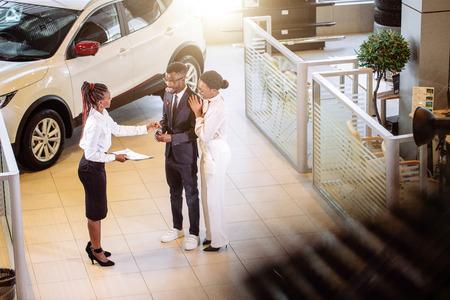 Autoverkäufer, der an der Verkaufsstelle steht, die Kunden über Eigenschaften des Autos erzählt Standard-Bild - 94925656