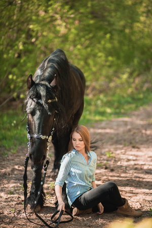 Handsome woman sitting on the ground with brown horse near her.