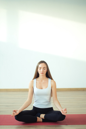 Young woman meditates while practicing yoga Stock Photo