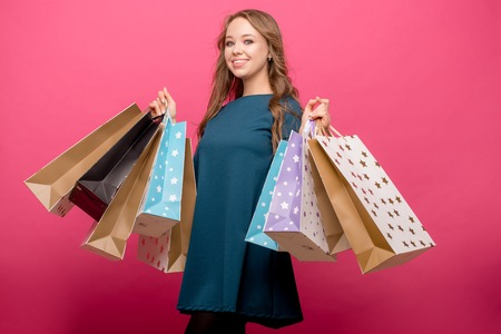 girl holding shopping bags and looking at camera isolated over pink background