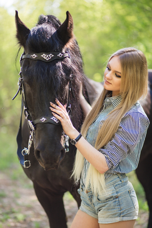 beautiful girl stroking horse outside Stock Photo