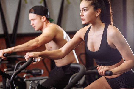 woman and man biking in gym, exercising legs doing cardio workout cycling bikes Stock Photo